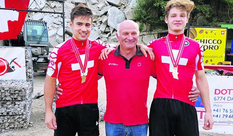 Tom Blaser et Romain Bellanger, membres du VTBJ et champions suisses 2017, entourent leur entraîneur Jean-Daniel Savary