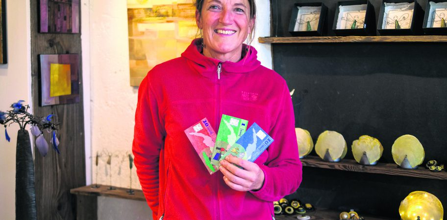 Lucie Weber, organisatrice, avec des billets de la monnaie locale « Léman » acceptés dans la boutique