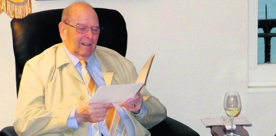 Marcel lisant les compliments de la commune de Puidoux avec quelques cadeaux sur les genoux dont un exemplaire du journal édité le jour de sa naissance le 4 janvier 1928